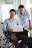 Mens in rolstoel holdingslaptop royalty-vrije stock afbeeldingen