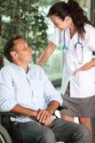 Mens in rolstoel met arts stock afbeeldingen
