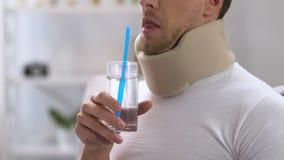 Mens in schuim cervicale kraag die water met stro, ongemak proberen te drinken stock footage