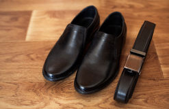 Mens set of black leather shoes and belt. On the floor Stock Images
