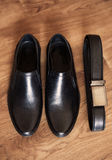 Mens set of black leather shoes and belt. On the floor Royalty Free Stock Images