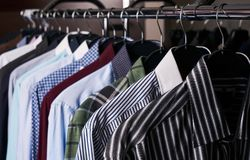 Mens shirts in different colors on hangers. In a retail clothes store. Men`s fashion, close-up stock photography