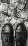 Mens shoes on a  scattered her paper money Royalty Free Stock Photography