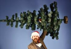 Mens in slim kostuum en Kerstmanhoed op blauwe achtergrond stock afbeeldingen