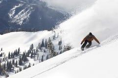 Mens Snowboarding onderaan Heuvel stock afbeelding
