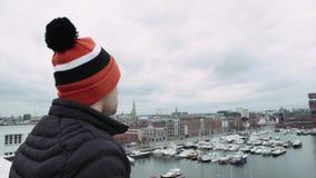 Mens in speciale kleurende hoed, die zich op barrière op dak bevinden die, afstand onderzoeken 4K stock videobeelden