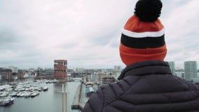 Mens in speciale kleurende hoed, die zich op barrière op dak bevinden 4K stock footage
