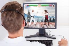 Mens Speel het Vechten Spel op Desktop Stock Afbeeldingen