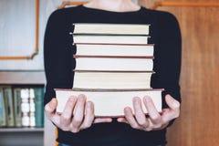 Mens, Student die vele boeken in handen op de achtergrond van boekenrekken houden De mannelijke handen houden een grote stapel bo royalty-vrije stock fotografie