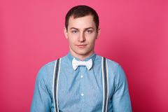 Mens style and fashion concept. Handsome blue eyed man with dark hair, smooth skin, wears shirt, bowtie and suspenders, looks at stock photography