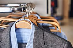 Mens suits and formal blue shirts on wooden hangers in a clothes store stock photography
