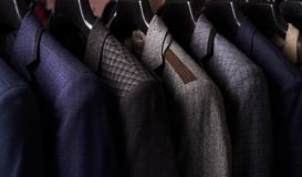 Mens suits on hangers in different colors Royalty Free Stock Photography
