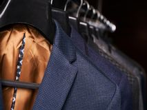 Mens suits on hangers in different colors Royalty Free Stock Image