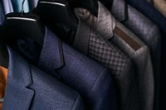 Mens suits on hangers in different colors Royalty Free Stock Photo