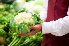 Mens in supermarkt als winkelmedewerker Stock Foto