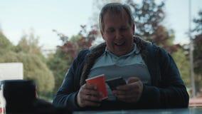 Mens in t-shirt met document kop van koffie surches Internet in zijn smartphone stock videobeelden