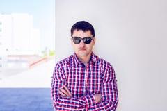 Mens tegen een muur, ernstige blik, zelfconcept In de zomer, de donkere glazen en een overhemd Stock Foto's