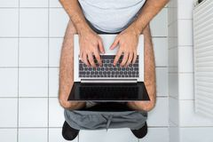 Mens in toilet die laptop met behulp van royalty-vrije stock foto