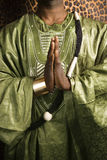 Mens in traditionele Afrikaanse kleding met handen samen. stock foto's