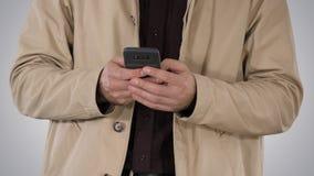 Mens in trenchcoat die mobiele smartphone op gradiëntachtergrond met behulp van stock foto