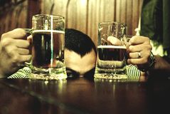Mens tussen bierglazen Stock Fotografie