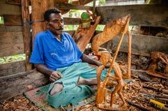 Mens van de Asmat-Stam die met een beitel een standbeeld snijden royalty-vrije stock foto's