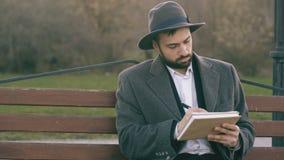 Mens van de Hipser de creatieve kunstenaar in hoed en laagtekening met pen en sketchbook zitting op de bank van de stadsstraat bi stock videobeelden