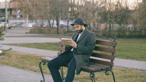 Mens van de Hipser de creatieve kunstenaar in hoed en laagtekening met pen en sketchbook zitting op de bank van de stadsstraat bi stock video
