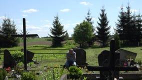 Mens van de wanhoops zit de rouwende zoon op bank dichtbij vadergraf in begraafplaats 4K stock videobeelden