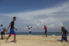 Mens van een het voetbalteam die van Havana op strand naar collega het knielen lopen Royalty-vrije Stock Afbeeldingen
