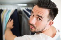 Mens van het kiezen van kleren tijdens het winkelen wordt vermoeid die Royalty-vrije Stock Fotografie