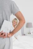 Mens verbergen huidig achter zijn rug voor gelukkige partner Royalty-vrije Stock Afbeeldingen