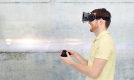 Mens in virtuele werkelijkheid hoofdtelefoon en gamepad het spelen Royalty-vrije Stock Foto