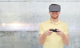 Mens in virtuele werkelijkheid hoofdtelefoon en gamepad het spelen Stock Afbeelding