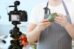 Mens Vlogger die Rijp Tropisch Avocadofruit tonen stock afbeelding