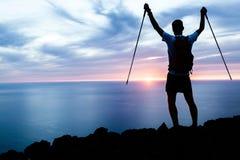 Mens wandelingssilhouet in bergen, oceaan en zonsondergang Royalty-vrije Stock Foto