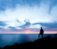 Mens wandelingssilhouet in bergen, oceaan en zonsondergang Stock Afbeelding