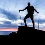 Mens wandelingssilhouet in bergen, oceaan en zonsondergang Stock Afbeeldingen
