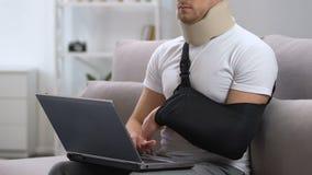 Mens in wapenslinger en cervicale kraag die aan laptop thuis werken, traumabehandeling stock footage