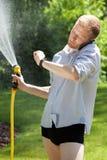 Mens water gegeven tuin en het spreken op de telefoon Stock Foto's