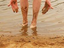 Mens in water met modderige benen en palmen Royalty-vrije Stock Afbeelding