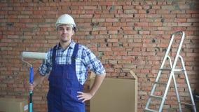 Mens in werken eenvormig in een witte helm, na een goede baan stock videobeelden