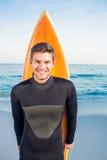 Mens in wetsuit met een surfplank op een zonnige dag Royalty-vrije Stock Foto