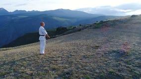 Mens in witte kimono en zwart band opleidingskarate op bergachtergrond lucht langzame motie 4k stock videobeelden