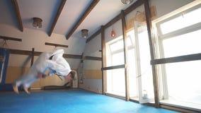 Mens in witte kimono met zwart band opleidingskarate in gymnastiek stock video