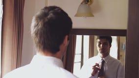 Mens in witte overhemdstribunes door de spiegel die een band binden Langzame Motie 3840x2160 stock videobeelden