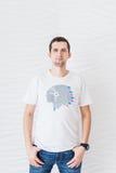 Mens in witte T-shirt en jeans op een witte achtergrond Royalty-vrije Stock Foto's
