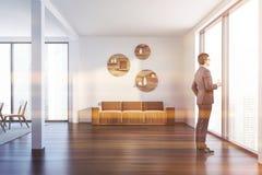Mens in witte woonkamer met beige bank stock foto