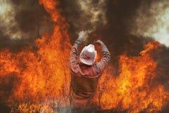 Mens in woedende vlam van brandbrandwond in gebieden, bossen en zwarte dikke bijtende rook De grote wildfire brandweerman van de  Stock Afbeeldingen