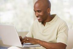 Mens in woonkamer die laptop met behulp van Stock Foto